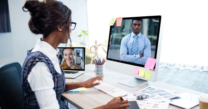 Comunicación video de la empresaria en el ordenador en oficina imagen de archivo libre de regalías