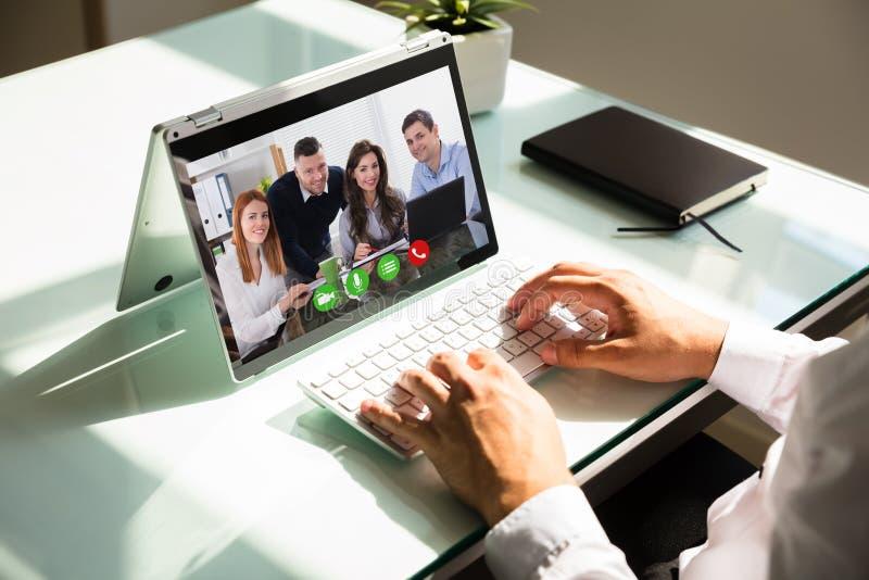 Comunicación video de la mano del hombre de negocios en el ordenador portátil fotos de archivo