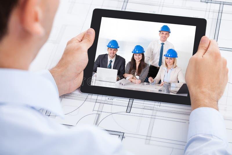 Comunicación video del arquitecto con el equipo con empuje foto de archivo libre de regalías
