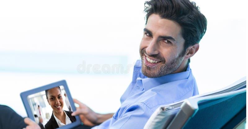 Comunicación video sonriente del hombre de negocios con el colega en la tableta imagenes de archivo