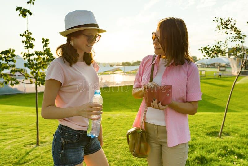 Comunicazione del genitore e dell'adolescente Generi i colloqui al suo adolescente della figlia, elimina la borsa con soldi dalla fotografia stock libera da diritti