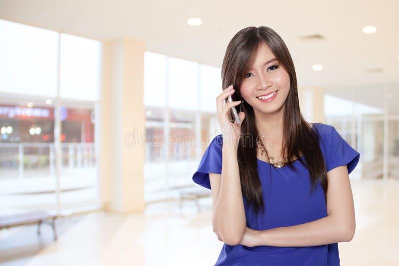 Comunicazione su mezzi mobili del bello imprenditore femminile asiatico fotografia stock