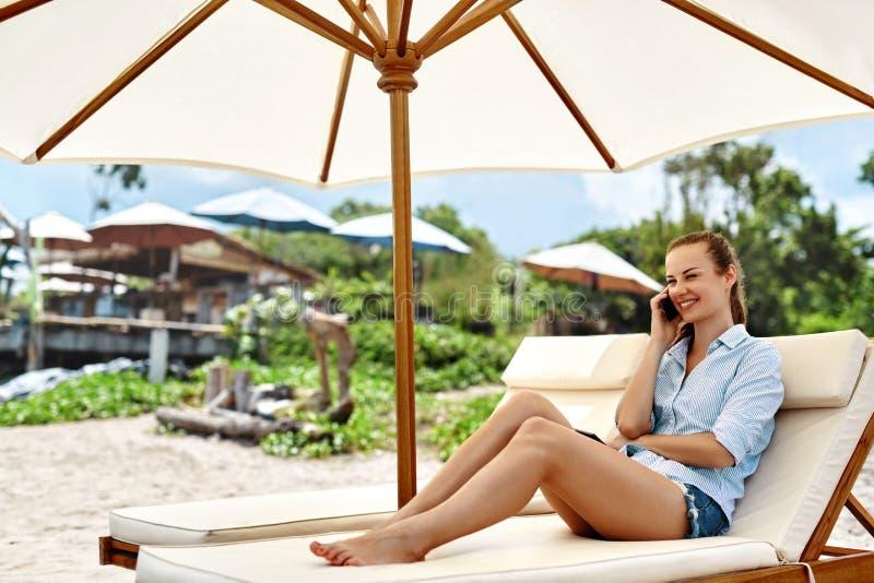Comunicazione su mezzi mobili Donna che invita telefono Spiaggia di estate freelance fotografie stock