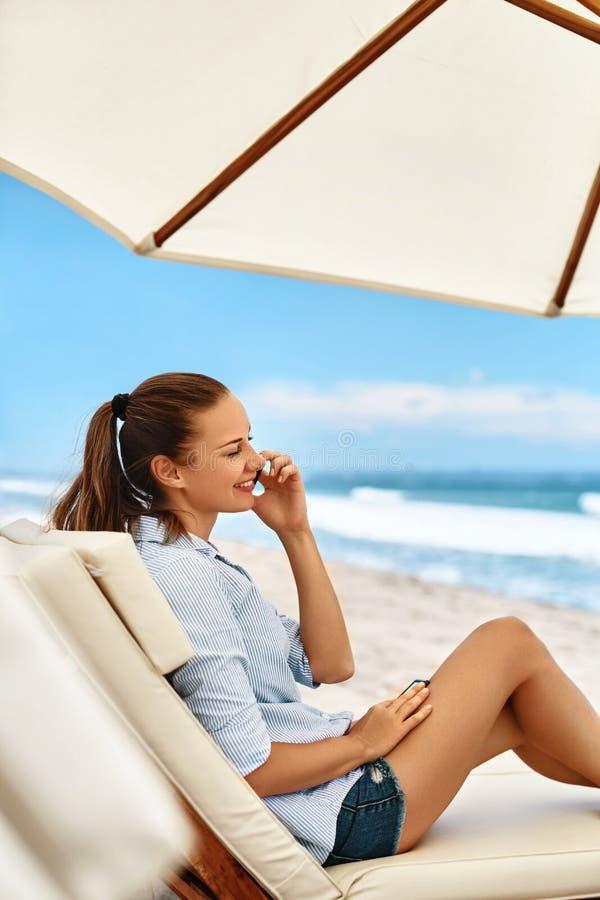 Comunicazione su mezzi mobili Donna che invita telefono Spiaggia di estate freelance fotografia stock libera da diritti