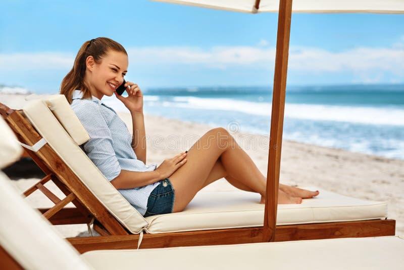Comunicazione su mezzi mobili Donna che invita telefono Spiaggia di estate freelance fotografia stock