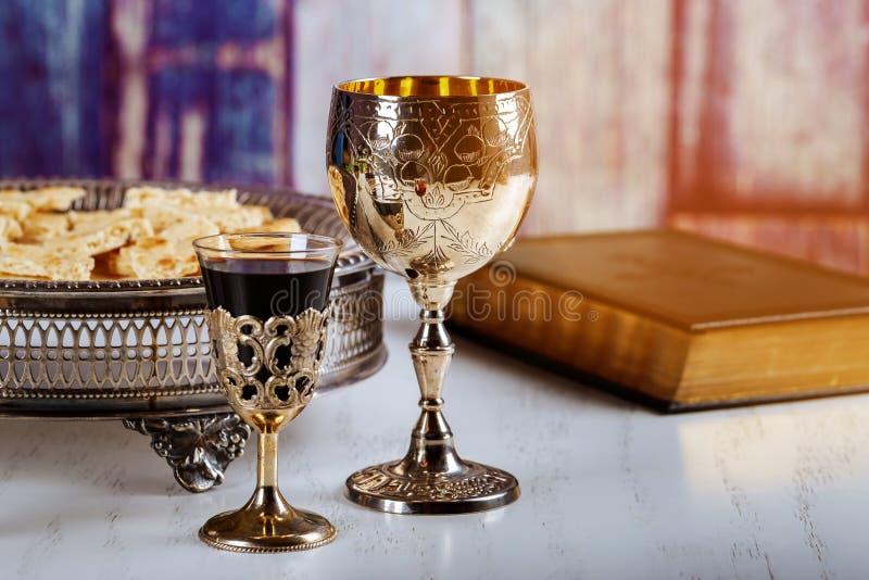 Comunione santa sulla tavola di legno sulla chiesa Tazza di vetro con vino rosso, pane sulla tavola di legno Bibbia santa immagine stock libera da diritti