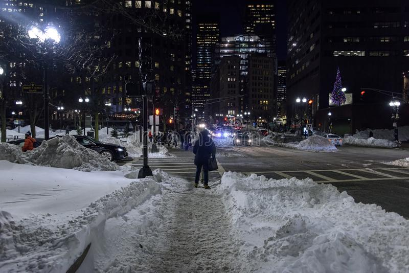 Comuters truggle home though the snow in downtown Boston stock images