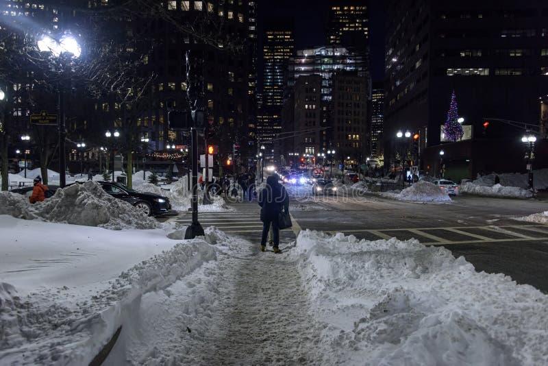 Comuters trugglehem fast den insnöade i stadens centrum Bostonen arkivbilder