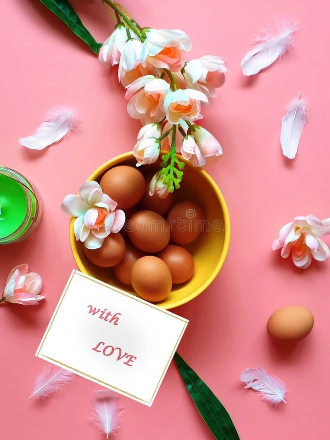 Con affetto piatto giallo della mela delle uova della cartolina d'auguri di Pasqua dei fiori della candela verde bianca rosa dell immagine stock