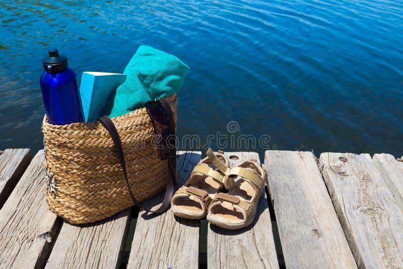 Con el bolso y el libro de la playa en el lago imagenes de archivo