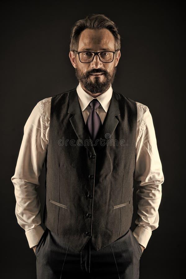 Con esperienza e saggio L'abbigliamento convenzionale classico dell'uomo d'affari si tiene per mano in tasche Il comportamento di immagine stock libera da diritti