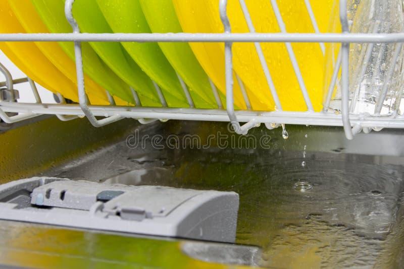 Con i piatti gialli luminosi vuoti le gocce dell'acqua nella lavastoviglie della porta della pentola, per ulteriore essiccazione fotografia stock