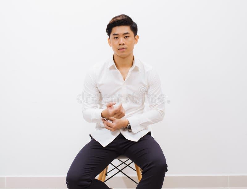 Con indifferenza bello Colpo dello studio del giovane bello che si siede sulla sedia e che esamina macchina fotografica con il so immagine stock
