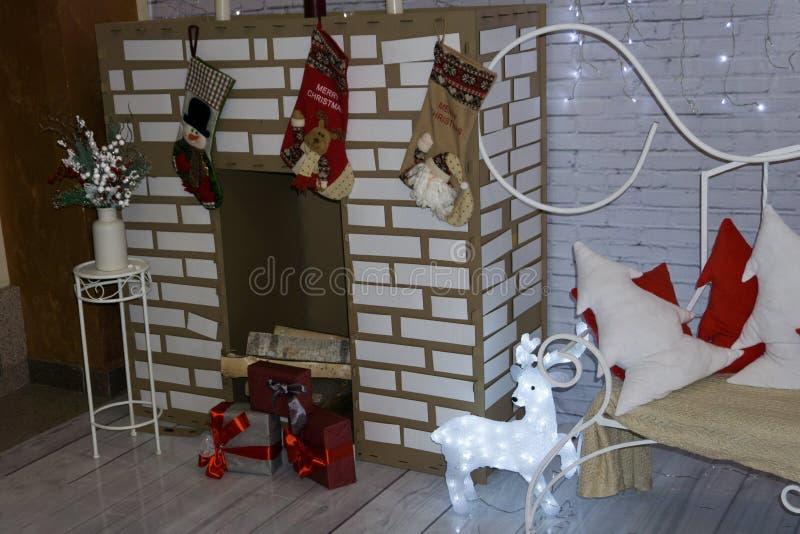 Con un árbol de navidad, una chimenea y regalos Una escena acogedora del invierno Interior blanco foto de archivo libre de regalías