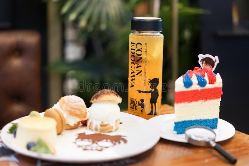 Conan署名甜点集合和在Conan题材在烘烤愿望装饰的果汁 免版税库存照片