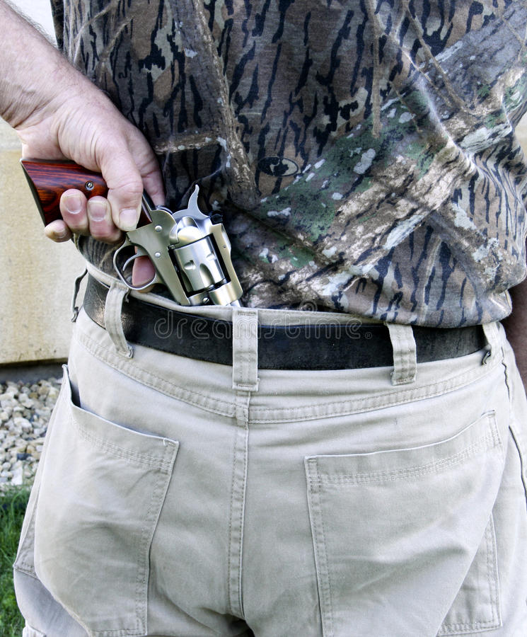 Concealed carried revolver. Man pulling a revolver pistol from his back stock image