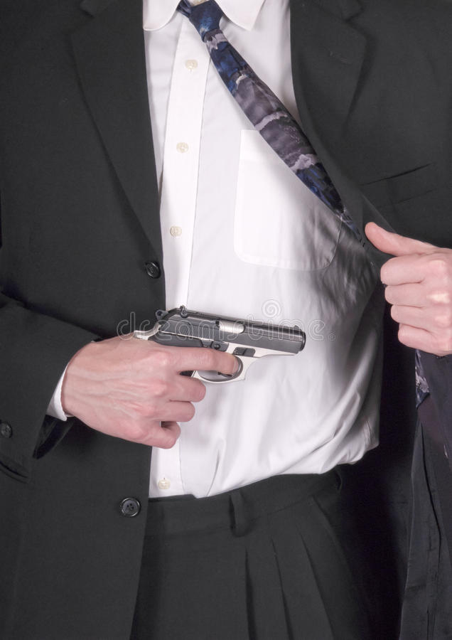 Concealed Weapon, Hand Gun, Pistol, Handgun. Concept for a man or male carrying a concealed weapon which is a small caliber hand gun. The handgun is tucked away stock image