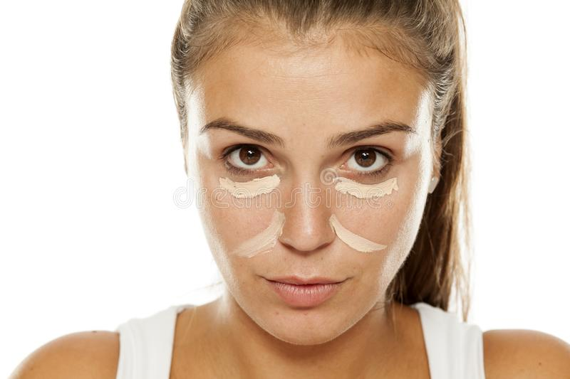 Concealer on her face. Young woman posing with concealer under her eyes and nose royalty free stock photo