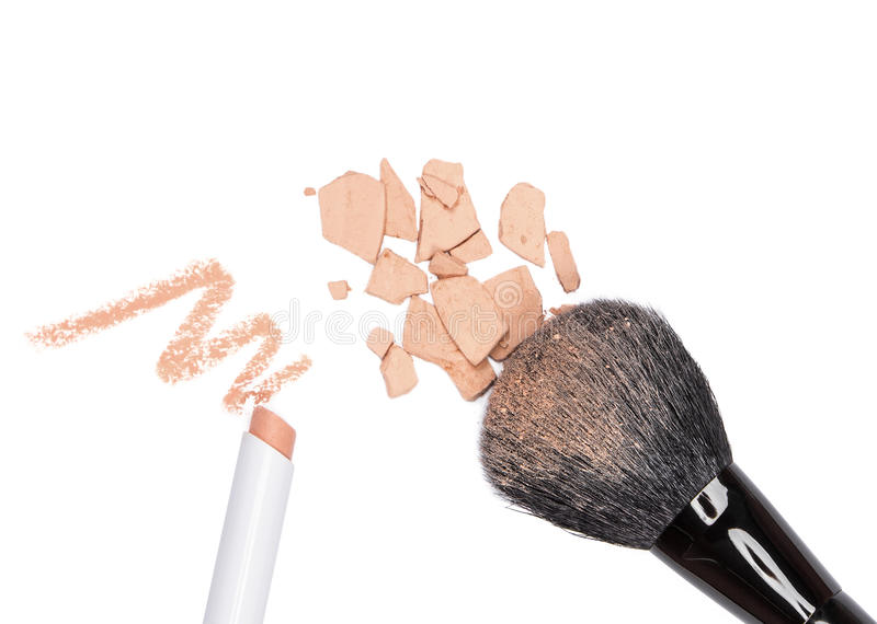 Concealer pencil and crushed compact cosmetic powder with makeup. Closeup of concealer pencil and crushed compact cosmetic powder with makeup brush on white stock photo