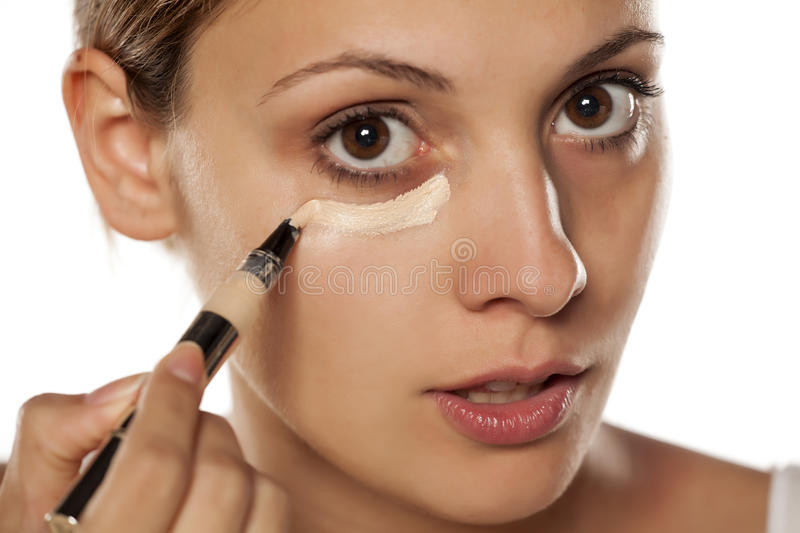 Concealer under her eyes. Young beautiful woman applying concealer under her eyes stock photography