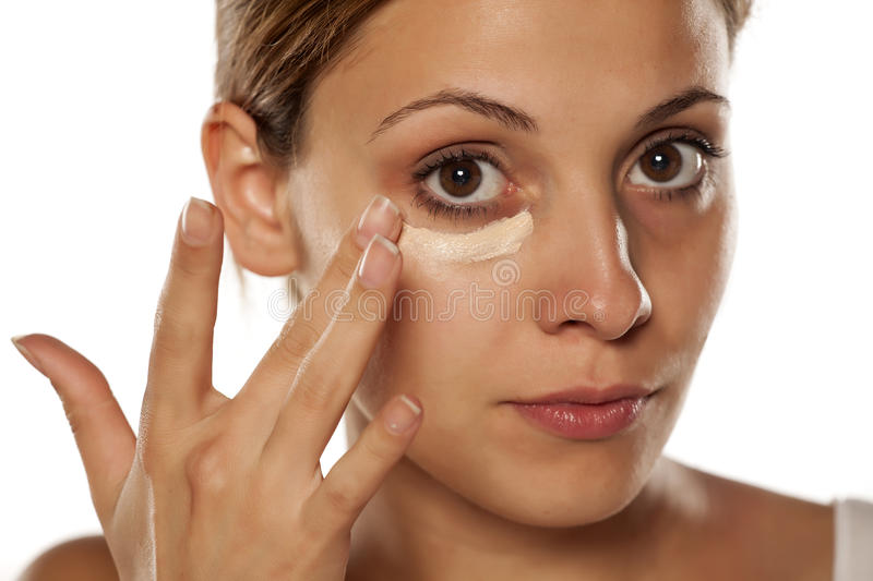 Concealer under her eyes. Young beautiful woman applying concealer under her eyes with her fingers royalty free stock photography