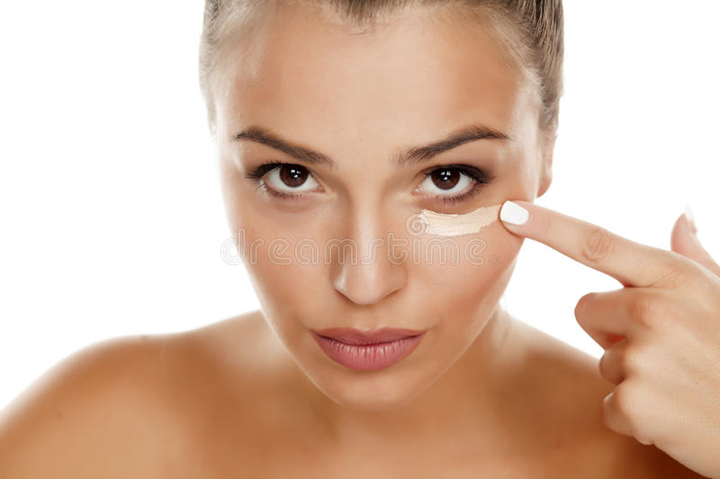 Concealer. Young woman applying concealer under the eye royalty free stock images