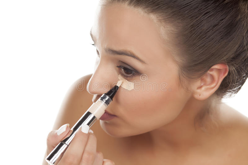 Concealer. Young woman applying concealer under the eye stock photos