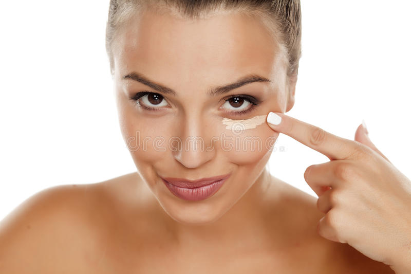 Concealer. Young woman applying concealer under the eye stock images