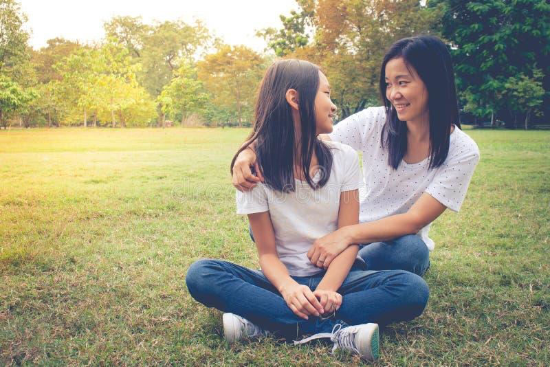 Conceito adorável: Felicidade de sorriso de aperto e de sentimento da mulher e da criança no parque imagem de stock royalty free