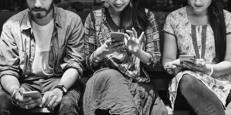 Conceito alegre ocasional do móbil dos amigos da afiliação étnica indiana imagem de stock