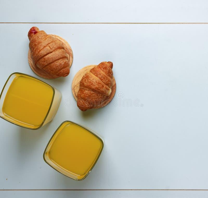 Conceito: alimento saudável, opinião superior do café da manhã saudável Suco de laranja e croissant Em um fundo azul fotos de stock