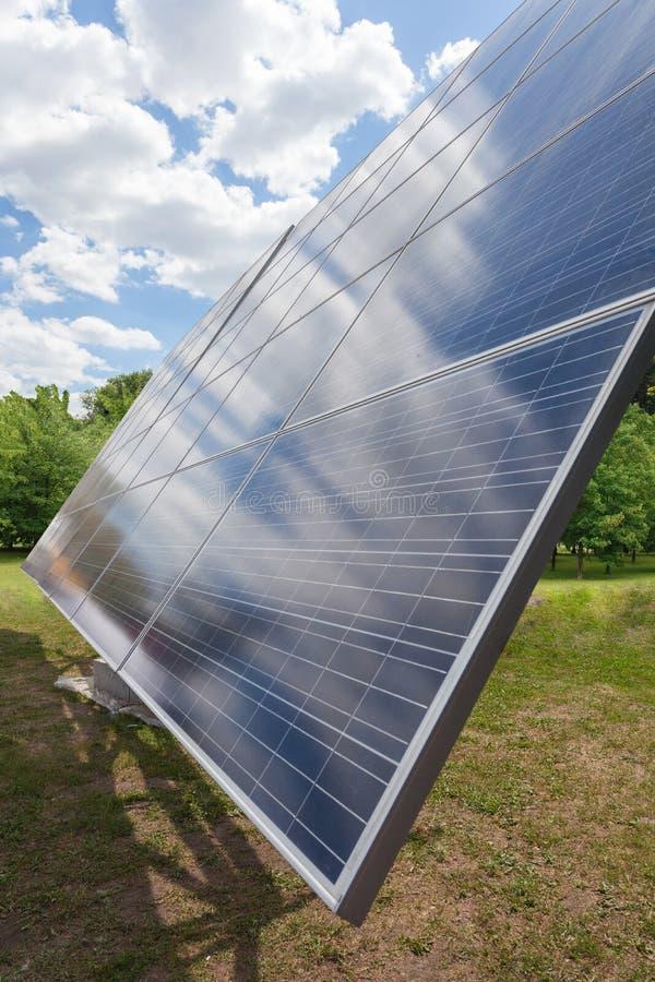 Conceito alternativo da energia do sol Foto vertical da vista lateral do elemento grande do painel solar contra na natureza verde fotos de stock
