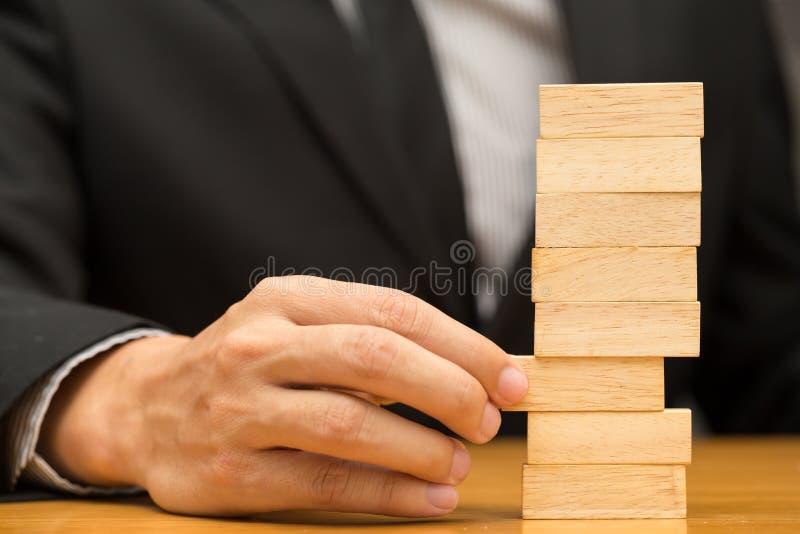 Conceito alternativo do risco Homem de negócios que escolhe o bloco de madeira imagem de stock