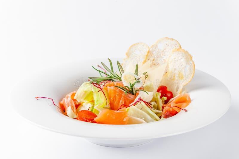 Conceito americano da culinária Salada de Caesar com salmões Placa branca em um fundo branco Imagem para um menu dos restaurantes imagens de stock