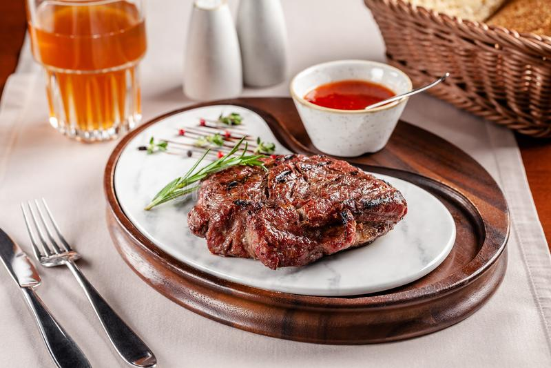 Conceito americano da culin?ria Bife da carne de porco com molho de assado vermelho do tomate Pratos de serviço em uma placa de m foto de stock