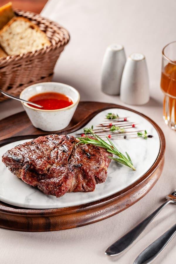 Conceito americano da culin?ria Bife da carne de porco com molho de assado vermelho do tomate Pratos de serviço em uma placa de m fotografia de stock