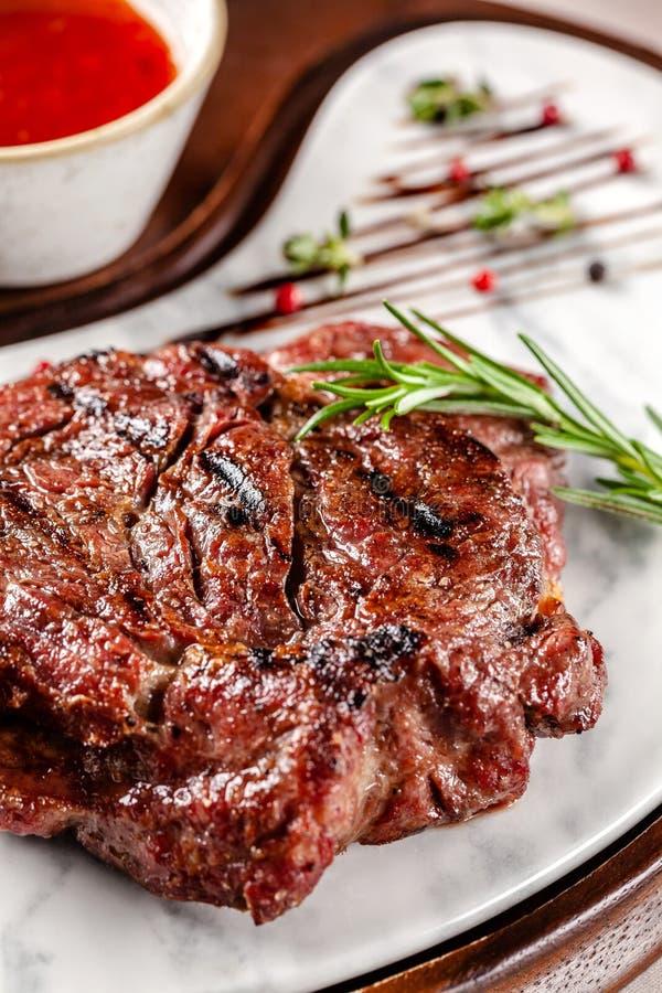 Conceito americano da culin?ria Bife da carne de porco com molho de assado vermelho do tomate Pratos de serviço em uma placa de m imagem de stock