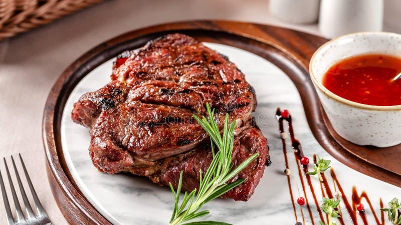 Conceito americano da culin?ria Bife da carne de porco com molho de assado vermelho do tomate Pratos de serviço em uma placa de m fotos de stock