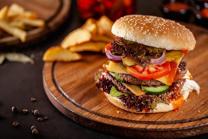 Conceito americano da culin?ria Um grande hamburguer caseiro com um rissol dobro da carne da carne de porco e da vitela, o tomate imagens de stock