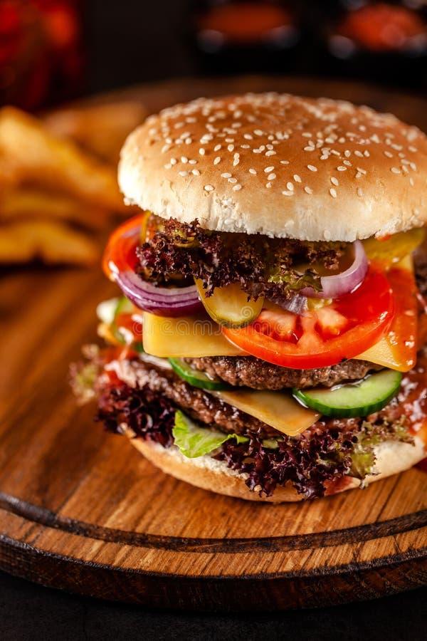 Conceito americano da culin?ria Um grande hamburguer caseiro com um rissol dobro da carne da carne de porco e da vitela, o tomate imagens de stock royalty free