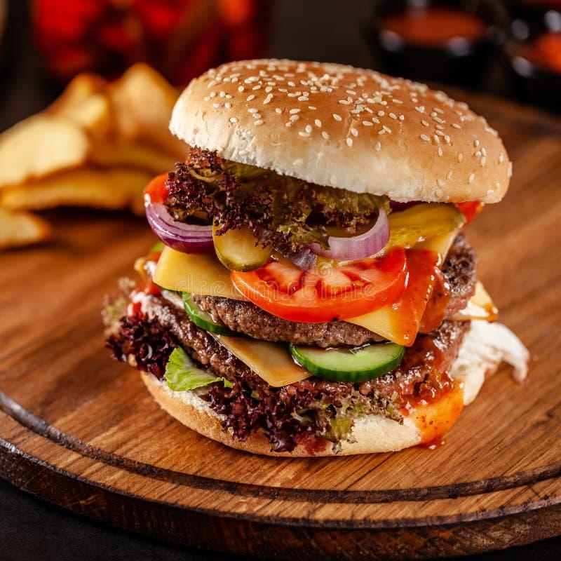 Conceito americano da culin?ria Um grande hamburguer caseiro com um rissol dobro da carne da carne de porco e da vitela, o tomate fotos de stock royalty free