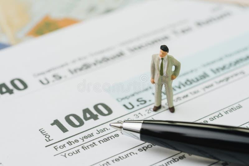 Conceito americano do cálculo do imposto, posição diminuta do homem de negócios foto de stock