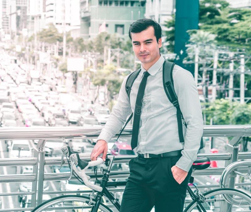 Conceito amigável do transporte do eco moderno, homem de negócio com a bicicleta na rua ocupada da cidade fotografia de stock royalty free