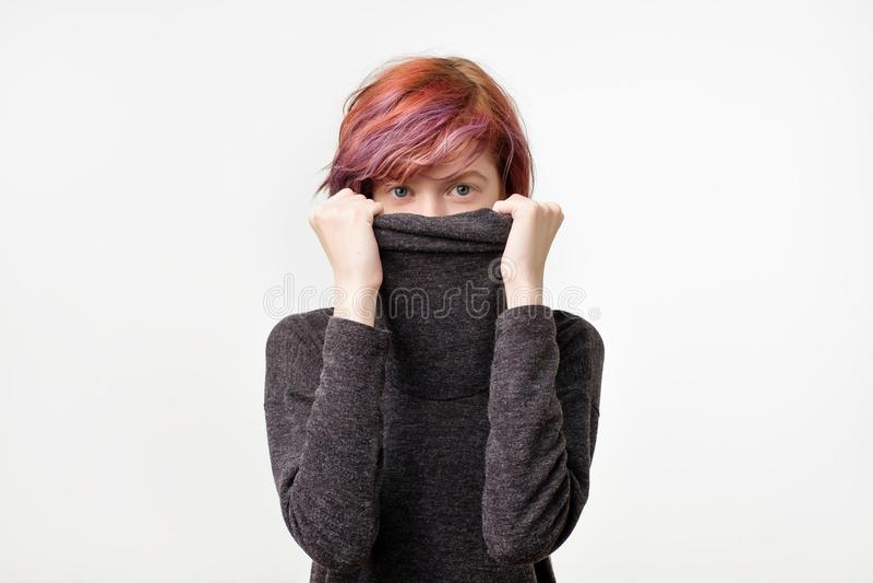 Conceito anônimo Jovem mulher com o penteado colorido interessante que esconde sua cara com colar imagem de stock