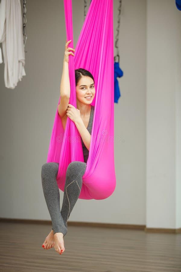 Conceito antigravitante aéreo da ioga, menina de sorriso relaxado na rede fotos de stock