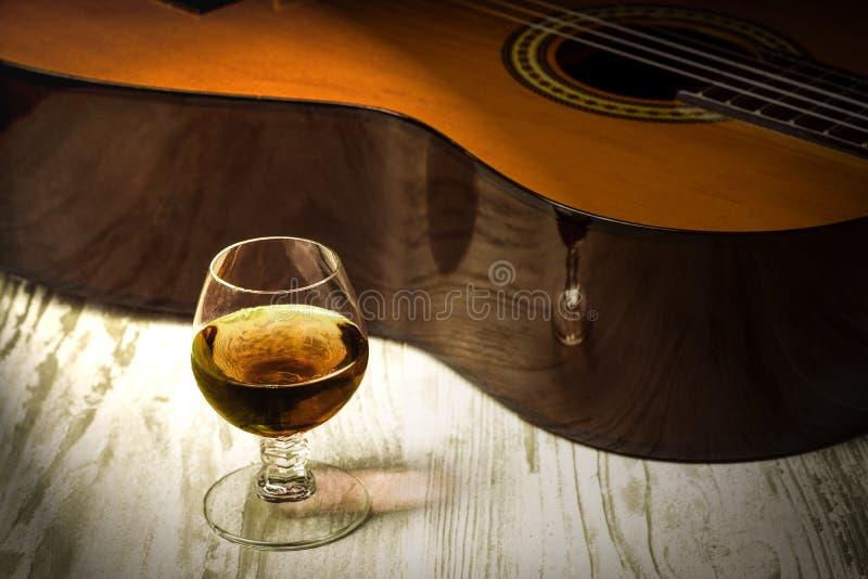 Conceito atrás da música a guitarra e o vidro do conhaque fotos de stock
