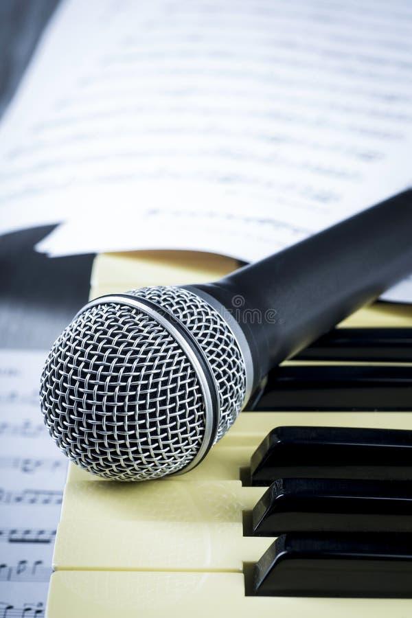 Conceito atrás da música o microfone e as chaves imagem de stock royalty free