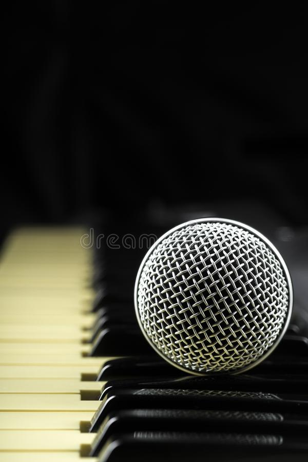 Conceito atrás da música o microfone e as chaves fotografia de stock royalty free