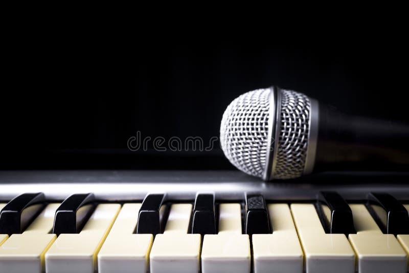 Conceito atrás da música o microfone e as chaves imagens de stock