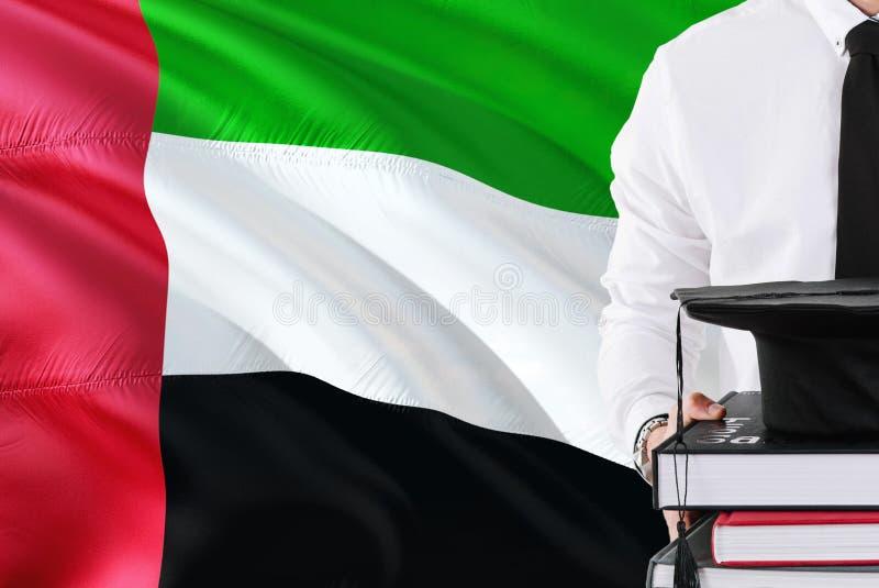 Conceito bem sucedido da educação do estudante Guardando livros e tampão da graduação sobre o fundo da bandeira de Emiratos Árabe imagem de stock royalty free